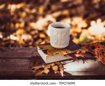 Hot coffee and red book with autumn leaves on wood background - seasonal relax concept .