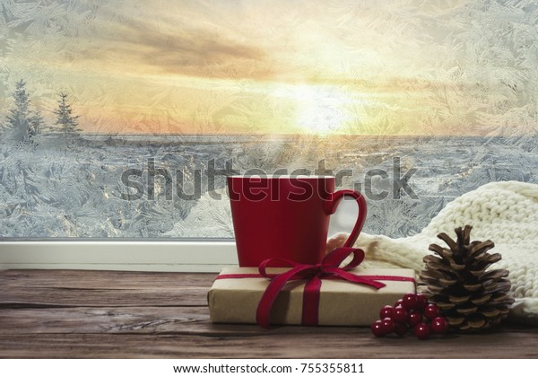 Hot coffee in red cup on a frosty winter day window background with gift, viburnum, fir cone and white knitted scarf.