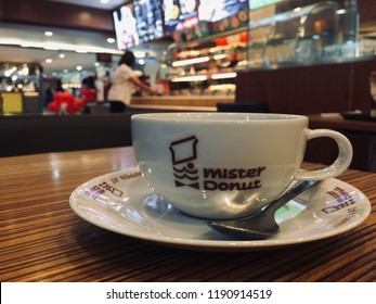 Hot coffee served in white ceramic cup and saucer with logo and word mister donut printed, blur payment counter in background. Mister donut shop in shopping mall, Bangkok. Thailand.  29 September 2018