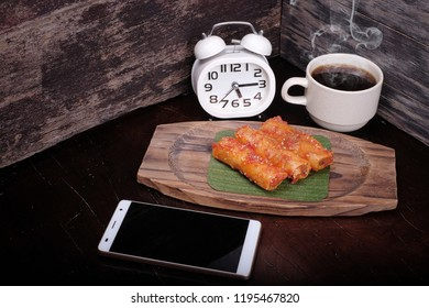 Hot coffee , smartphone  and alarm clock with popia on the table : Concept for coffee time