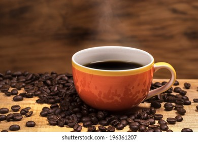 hot coffee with stream and coffee beans on wooden table