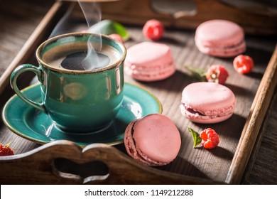 Hot coffee and tasty pink macaroons made of fresh raspberries