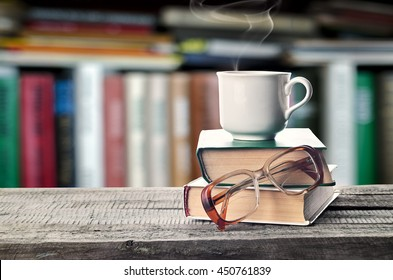 Hot coffee or tea, cocoa, chocolate cup on book and eyeglasses with copy space for text against the background of a bookshelf. Pile of books, glasses and cup on a table in the library