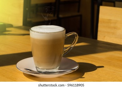 Hot Coffee in Transparent Cup with Froth and Smoke on Wooden Table with Beautiful Aura Light and Shadow, Set as Copy Space for Text.