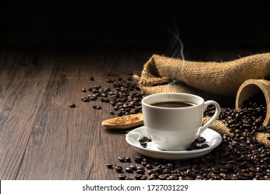 Hot coffee in a white coffee cup and many coffee beans placed around and sugar on a wooden table in a warm, light atmosphere, on dark background, with copy space.