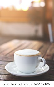 Hot coffee in white cup on wooden table. added rim light.