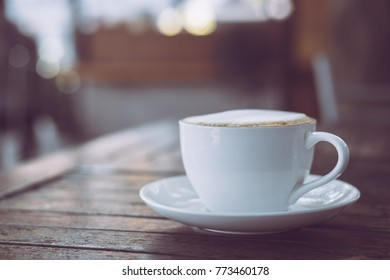 Hot coffee in white cup on wooden table