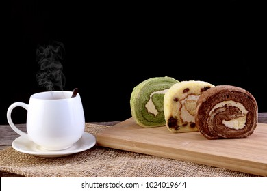 Hot Coffee in the white cup with smoke, and Yam Roll Cake include Matcha green tea, Currants, Chocolate with white cream inside, on wooden board background. Foods and drinks concept. Black background.
