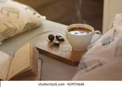Hot coffee in a white mug with a nice smoke on the wooden coaster, dark chocolate pieces and an open book in bed. Grey sheet and soft pillow background. Morning light. Toned picture. Vintage look.