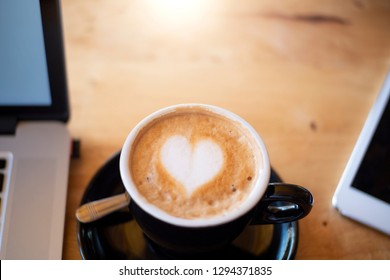hot coffee write heart shape and laptop background