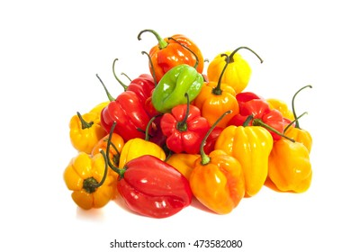Hot colorful chili peppers on a pile over white