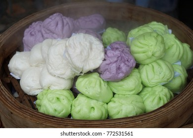 Hot colorful steam buns on the traditional bamboo pan