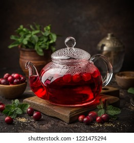 hot cranberry drink in glass tea pot, dark background, selective focus, square image