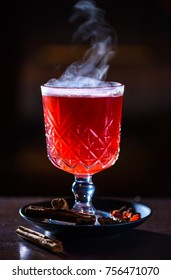 Hot cranberry drink with lemon, cinnamon and other spices on dark background