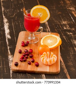 Hot cranberry drink on wooden background