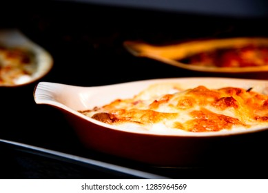 Hot creamy potato gratin with cheese in oven.