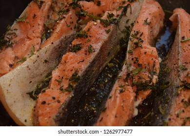 Hot crispy salmon with seasoning sizzling in a hot oily pan