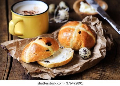 Hot cross buns with butter for Easter with quail eggs and cappuccino on rustic wooden background