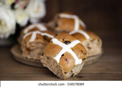 Hot cross buns with flowers behind.  Easter treats on old board with timber background. Focus on front bun. Shallow depth of field. Large File.
