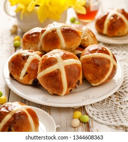 Hot cross buns, freshly baked hot cross buns on a white plate on a wooden table. Traditional easter food