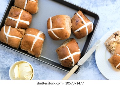 Hot cross buns on baking tray with butter and buttered bun and knife.