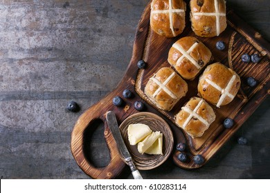 Hot cross buns on wooden cutting board served with butter, knife, fresh blueberries and jug of cream over old texture metal background. Top view, space. Easter baking.