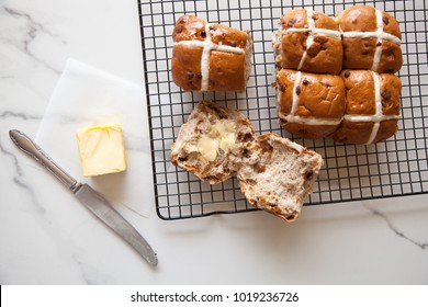 Hot Cross Buns, six Easter Buns with butter and knife on marble bench top with wire rack