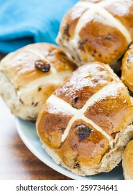 Hot cross buns, Spiced sweet bread coated in honey piled on a blue plate