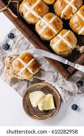 Hot cross buns in wooden tray served with butter, fresh blueberries, knife and jug of cream on textile napkin over white texture concrete background. Top view, space. Easter baking.