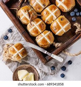 Hot cross buns in wooden tray served with butter, fresh blueberries, knife and jug of cream on textile napkin over white texture concrete background. Top view, space. Easter baking. Square image
