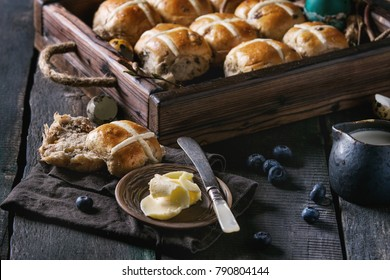 Hot cross buns in wooden tray served with butter, knife, blueberries, easter eggs, birch branch, jug of cream on textile napkin over old texture wood background. Dark rustic style. Easter baking.