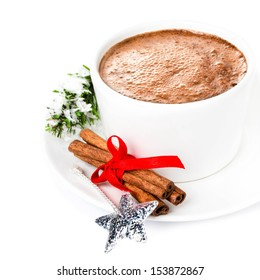 Hot cup of cappuccino, christmas ball,  cinnamon sticks and tree branch isolated on white, closeup.  Bright Christmas composition