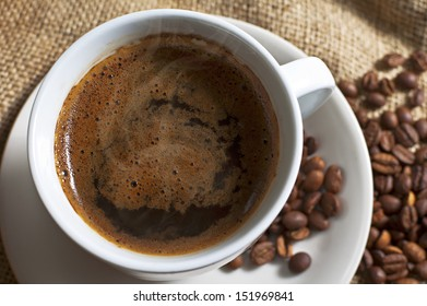 Hot cup of coffee with coffee beans on canvas. Selective focus with shallow depth of field.