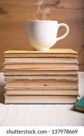 A hot cup of coffee on a stack of books