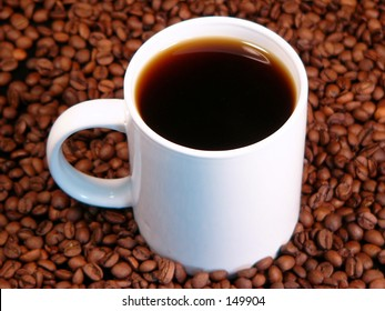 a hot cup of coffee surrounded by whole coffee beans