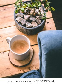 Hot cup of coffee in a white ceramic mug on an aged wooden coffee table. Blue Armchair and Bonsai tree with stones in background.