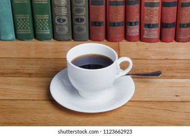 Hot cup of fresh coffee on the wooden table and  stack of books to read
