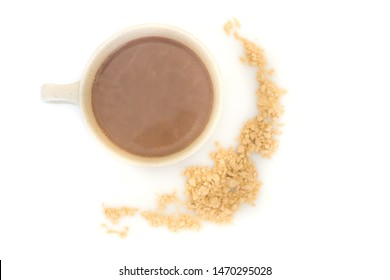 A hot cup of maca latte, made from maca powder, a Peruvian superfood good for hormone regulation. Isolated on a white background, with maca powder sprinkled around the mug.