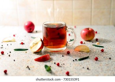 hot Cup of tea with apples, spices, leaves and rowan berries