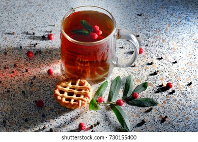 a hot Cup of tea with cake and rowan berries