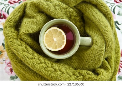 Hot cup of tea in warm green scarf