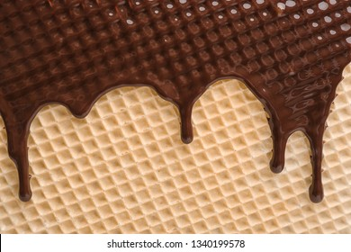 Hot dark chocolate on wafer, closeup. Crispy food