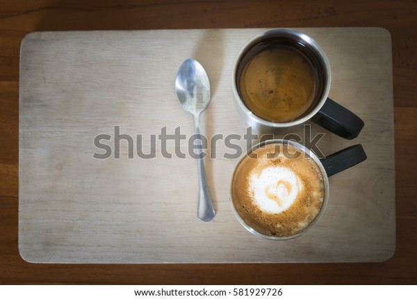 Hot dark coffee in stainless cup with cup of hot tea and stainless spoon on the wood. Dark coffee concept.