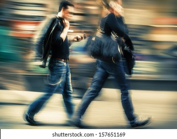 Hot day in the city. Man and woman talking on a cell phone in a hurry. Intentional motion blur and color shift