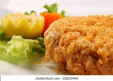 Hot and delicious fried meat on white dish, closeup.