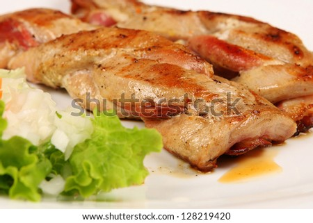 Hot and delicious roasted meat on white dish, closeup.