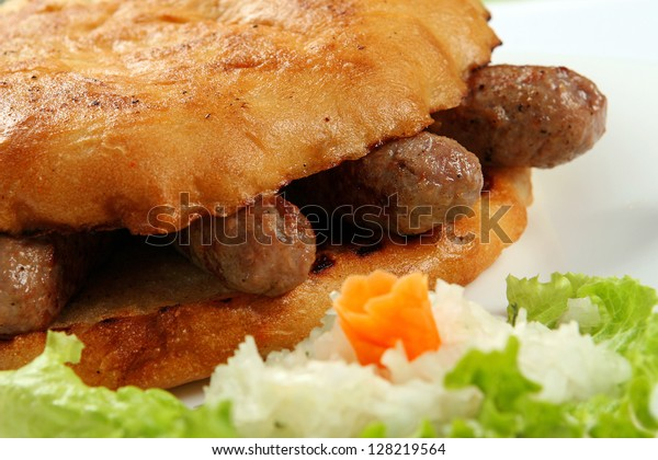 Hot and delicious, traditional bosnian food Cevapcici on white dish, closeup.