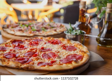 Hot delicous pepperoni pizza on wooden restaurant table.