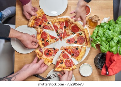 Hot delicous pepperoni pizza on wooden restaurant table. Poeple share pizza.
