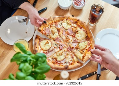 Hot delicous pizza with pear and blue cheese on wooden restaurant table. People hands taking slices of pizza.